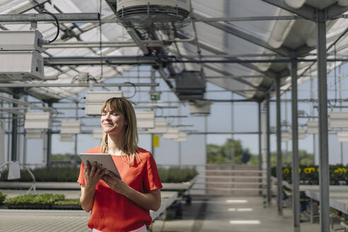 Smiling female entrepreneur with eyes closed holding digital tablet while standing in greenhouse - JOSEF01763