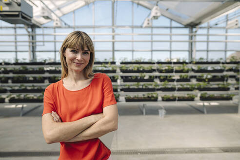 Smiling female entrepreneur with arms crossed standing against plants at nursery - JOSEF01769