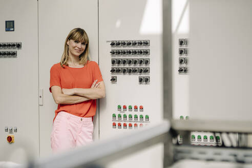 Female entrepreneur with arms crossed standing by control panel in greenhouse - JOSEF01778