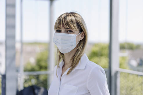 Close-up of female entrepreneur wearing mask standing in greenhouse - JOSEF01817