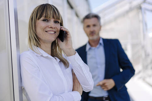 Smiling businesswoman talking over smart phone while male coworker standing in background - JOSEF01835