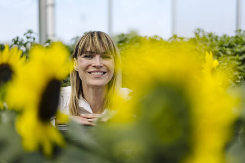 Close-up of smiling businesswoman with plants in greenhouse - JOSEF01844