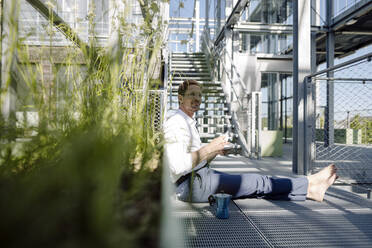 Male professional with coffee relaxing on floor in plant nursery - JOSEF01883