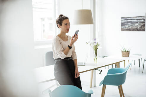 Businesswoman using mobile phone while standing by table - JOSEF01906