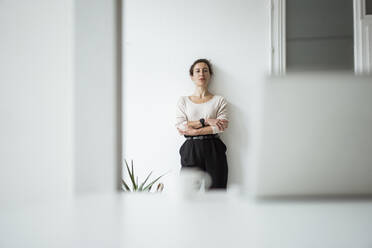Serious businesswoman with arms crossed standing against white wall - JOSEF01909