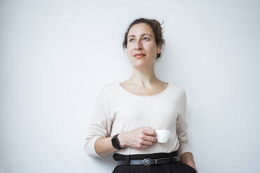 Thoughtful businesswoman holding coffee cup standing against white wall - JOSEF01912