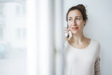 Businesswoman talking over mobile phone seen through window - JOSEF01915