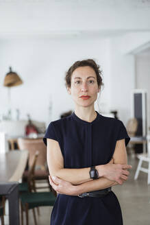 Confident female owner with arms crossed standing in restaurant - JOSEF01924