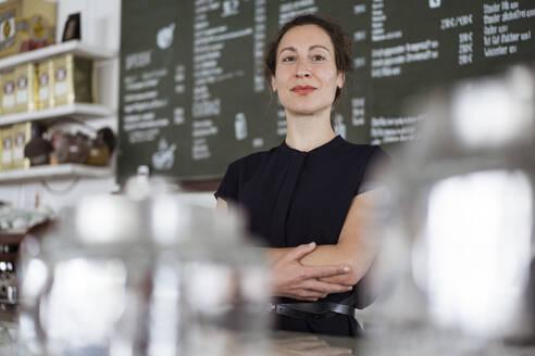 Confident female owner standing against blackboard in coffee shop - JOSEF01927