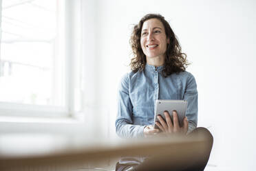 Smiling businesswoman using digital tablet while sitting against wall - JOSEF01945