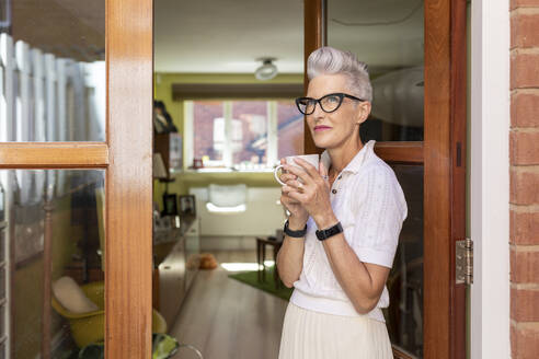 Contemplating senior woman standing on doorway while drinking coffee at home - WPEF03331
