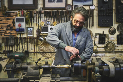 Focused mature bearded goldsmith in eyewear working on polishing machine in workshop while holding pointed metal stick - ADSF15426