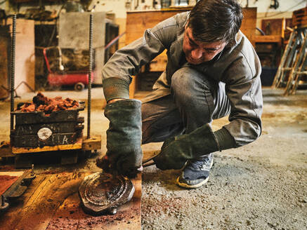 Professional mature craftsman in workwear and protective gloves cleaning metal casting removed from sand mold while working in goldsmith workshop - ADSF15447