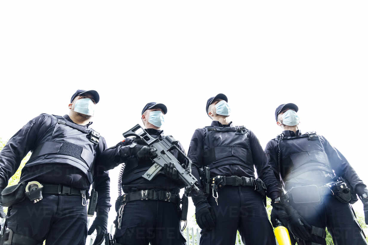 Full Body Squad Of Spanish Police Officers In Protective Gears With Guns Wearing Medical Masks During
