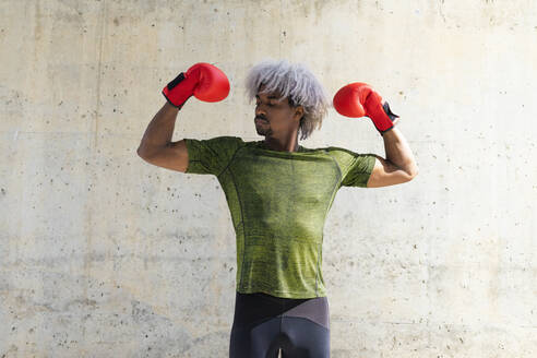 Powerful African American sportsman in boxing gloves demonstrating biceps against weathered wall during workout on street - ADSF15519