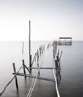 Abandoned partially destroyed dock made of thick wooden sticks on endless ocean with pure water under serene sky in daylight - ADSF15576