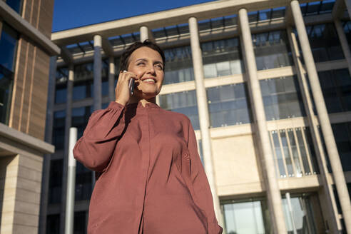 Businesswoman talking on smart phone while standing against building - VPIF03026