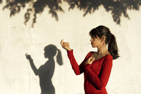 Contemplating woman doing hand gesture while standing by tree shadow - TCEF01046