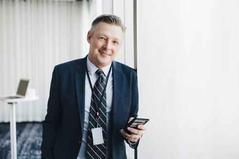 Portrait of smiling entrepreneur with mobile phone in office - MASF19851