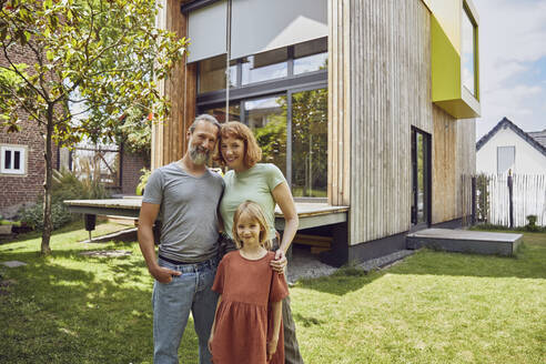 Smiling daughter standing with parents against tiny house in yard - MCF01322