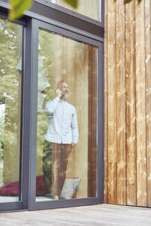 Mature man talking over smart phone while standing in tiny house seen through window - MCF01385