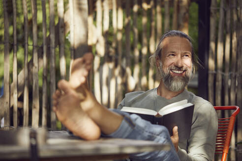 Smiling bearded man reading book while relaxing on chair in yard - MCF01403