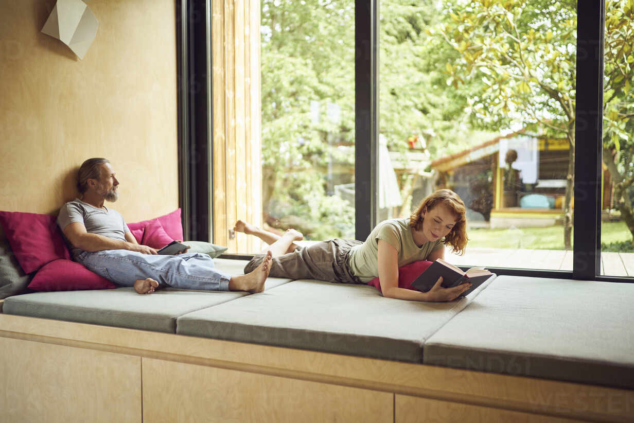 Woman reading book while man sitting with digital tablet on bed by window  at home - MCF01454 -