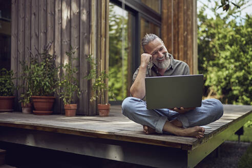 Smiling mature man using laptop while sitting against tiny house - MCF01469