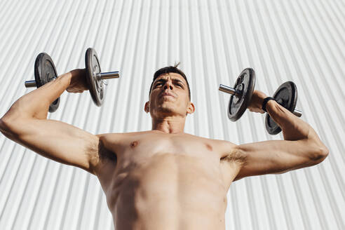 Shirtless man picking dumbbell while standing against wall - MIMFF00196