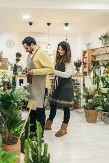 Woman helping man to wear apron while standing at flower shop - MRRF00395