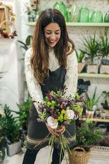 Woman smiling while holding bunch of flowers at flower shop - MRRF00401