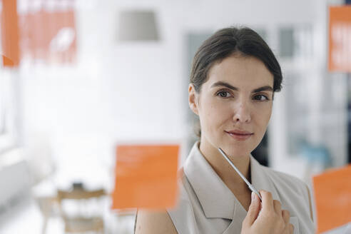 Businesswoman brainstorming while standing at office - KNSF08434