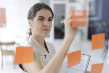 Woman writing on sticky note while standing at office - KNSF08437