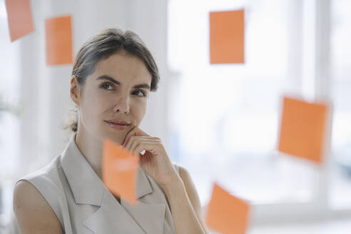 Businesswoman brainstorming while standing by glass wall at office - KNSF08443