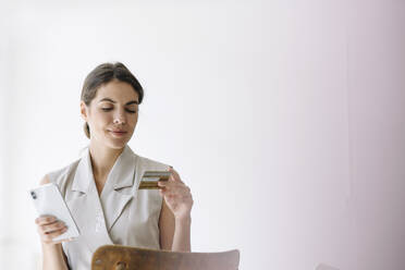 Smiling businesswoman holding credit card while using mobile phone at office - KNSF08461