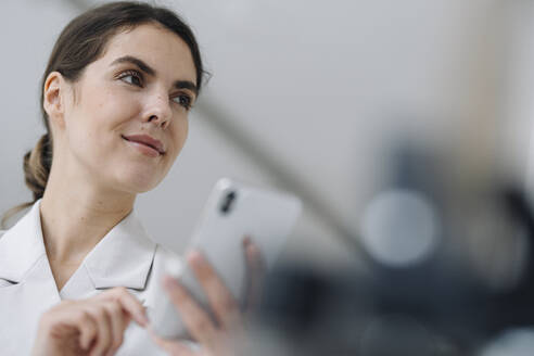 Businesswoman using mobile phone at office - KNSF08464