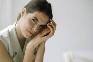Young woman with head in hands sitting at office - KNSF08488