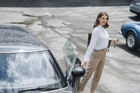 Businesswoman opening door of car while standing at parking lot - KNSF08515