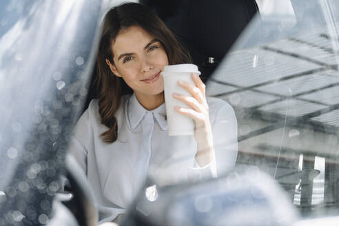 Smiling woman drinking coffee while sitting in car - KNSF08518