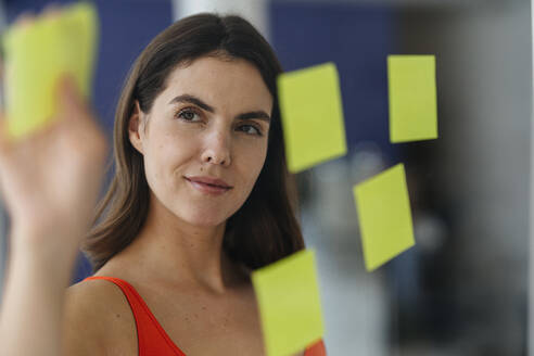 Woman putting sticky note on glass wall at home - KNSF08539
