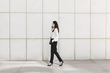 Businesswoman walking while talking on smart phone in city - MRRF00419