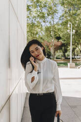 Smiling businesswoman standing in city while talking on smart phone - MRRF00422