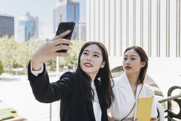 Female colleagues taking selfie on smart phone against financial district in city during sunny day - MRRF00431