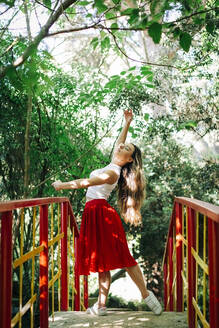 Young woman practicing ballet on footbridge against trees in park - DCRF00821