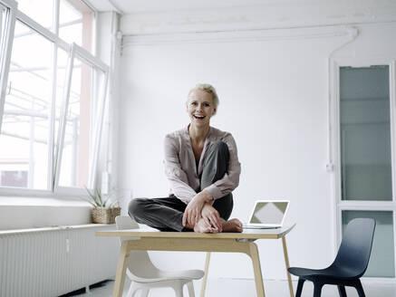 Cheerful businesswoman sitting on desk in loft office - KNSF08570