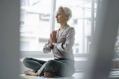 Businesswoman with eyes closed meditating while sitting against window in loft office - KNSF08627