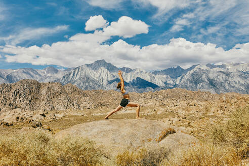 Young woman practicing yoga near Alabama Hills in northern California. - CAVF88872