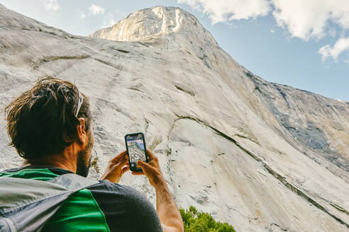 Young man taking picture of El Capitan Mountain in Yosemite Park. - CAVF88878