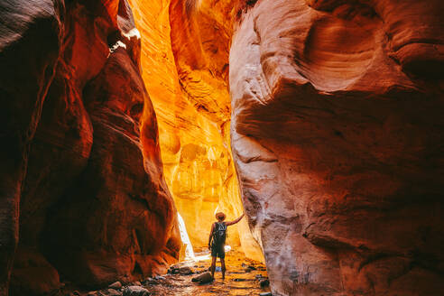Young man wearing a hat, exploring a slot canyon in Kanarra Fall, Utah - CAVF88908