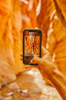 Young man's hand taking picture of slot canyons in Kanarra Falls - CAVF88911